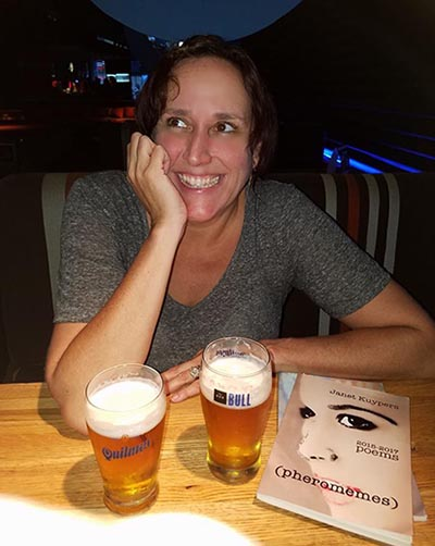 "photo of Janet Kuypers with her book ""(pheromemes) 2015-2017 poems"" at Bar Bull Resto-Pub in Buenos Aures"