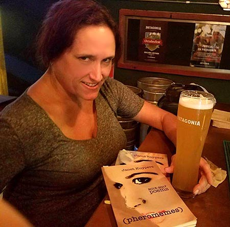 "photo of Janet Kuypers with her book ""(pheromemes) 2015-2017 poems"" at Patagonia Brewingin Buenos Aures"